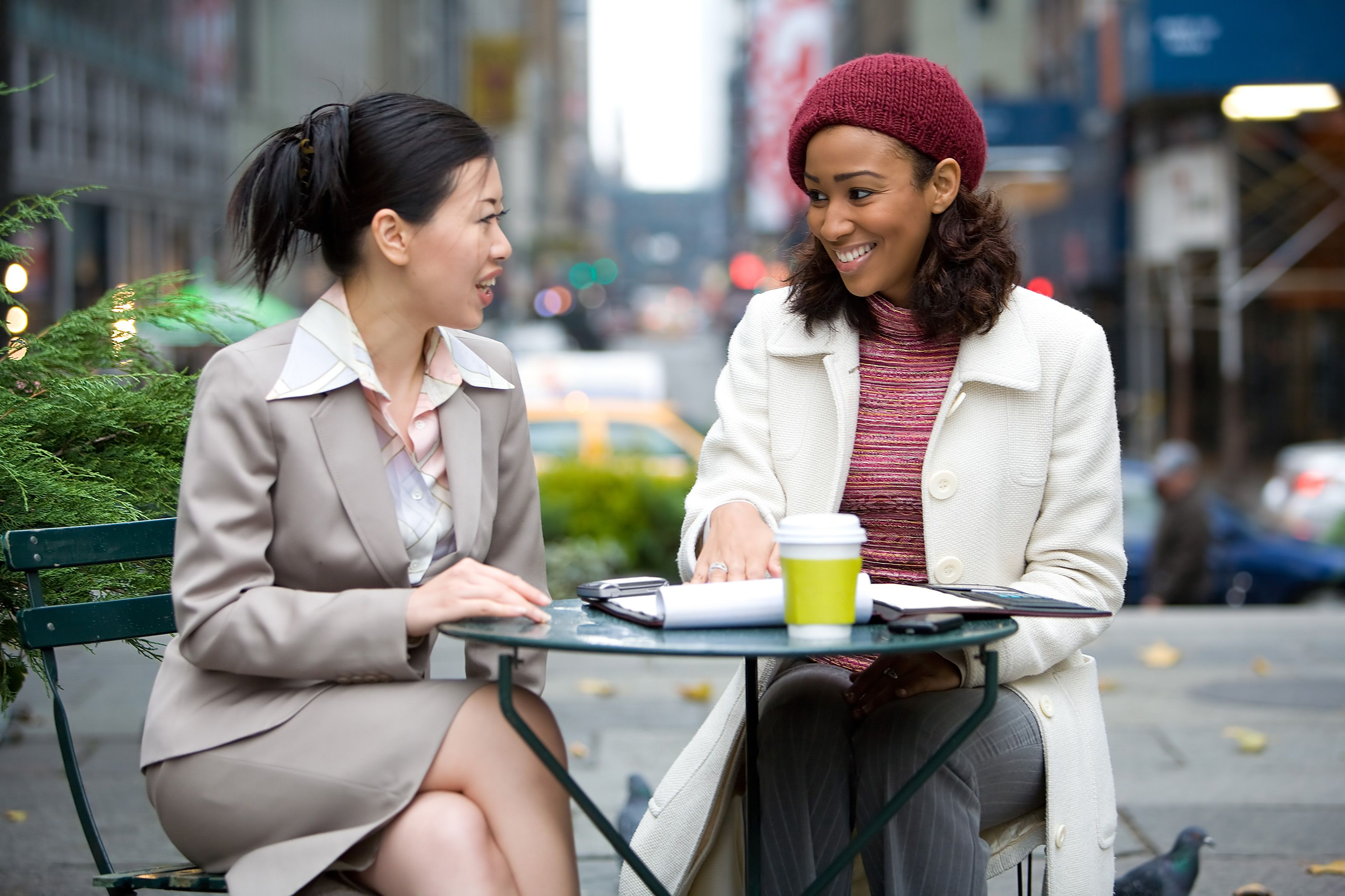 Two business women having a casual meeting or discussion in the city