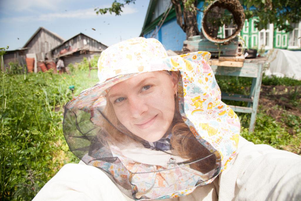 Woman beekeeper making selfie near beehives